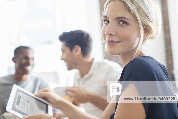 Geschäftsfrau mit digitalem Tablett bei der Besprechung
