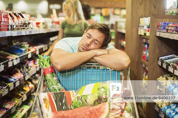 Mann schläft auf Einkaufswagen im Lebensmittelgeschäft