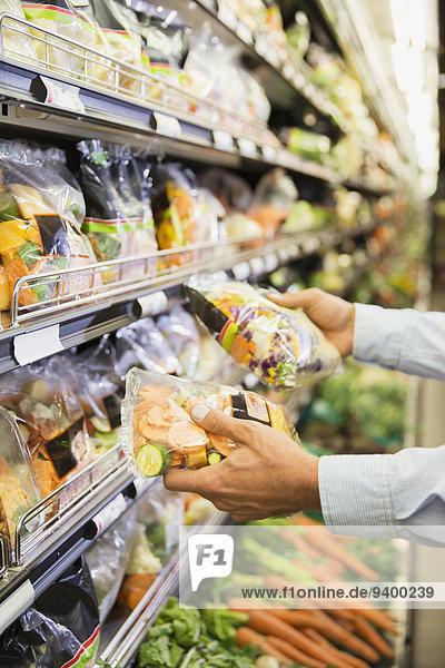 Nahaufnahme des Mannes beim Vergleich von Produkten im Lebensmittelgeschäft