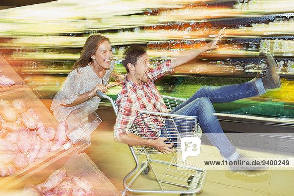 Verschwommene Ansicht des Paares  das mit dem Einkaufswagen im Lebensmittelladen spielt.