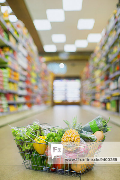 Nahaufnahme des vollen Einkaufskorbes auf dem Boden des Lebensmittelladens