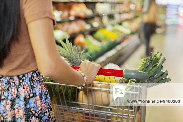 Nahaufnahme einer Frau  die einen vollen Einkaufswagen im Lebensmittelgeschäft schiebt.