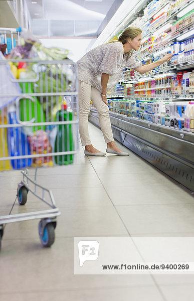 Frau untersucht Produkte im Lebensmittelgeschäft