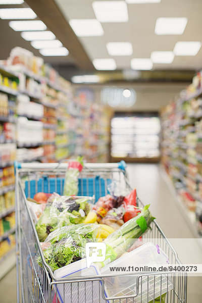 Voller Einkaufswagen im Lebensmittelgang