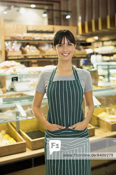 Verkäuferin lächelt an der Theke des Lebensmittelgeschäftes