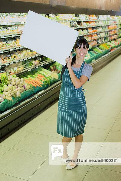 Angestellter  der eine leere Karte im Lebensmittelgeschäft aufbewahrt