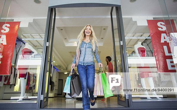 Ansicht der Frau  die Einkaufstaschen aus dem Bekleidungsgeschäft trägt.