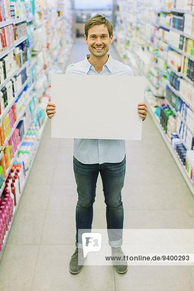 Mann mit leerer Karte im Gang des Lebensmittelgeschäfts