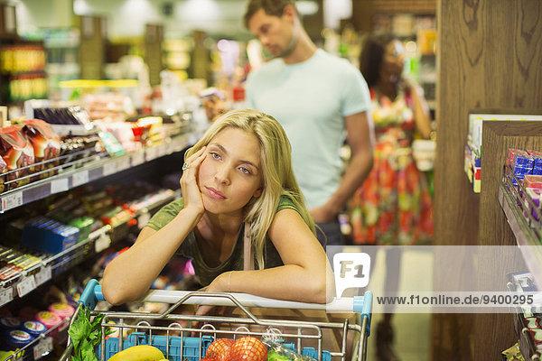 Gelangweilte Frau beim Einkaufen im Lebensmittelgeschäft