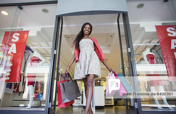 Ansicht der Frau  die Einkaufstaschen aus dem Bekleidungsgeschäft trägt. Ansicht der Frau, die Einkaufstaschen aus dem Bekleidungsgeschäft trägt.
