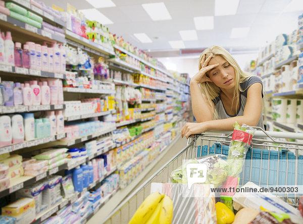 Frustrierte Frau schiebt Einkaufswagen im Lebensmittelladen