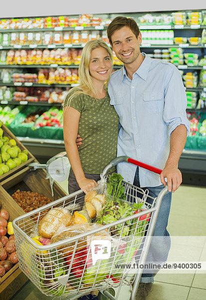 Paar lächelnd mit vollem Einkaufswagen im Lebensmittelgeschäft
