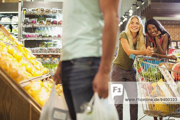 Frauen bewundern Männer beim Einkaufen im Lebensmittelgeschäft