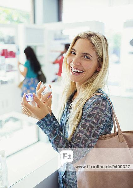 Frau probiert Parfüm in der Apotheke an