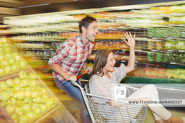 Blurred view of couple playing in grocery store