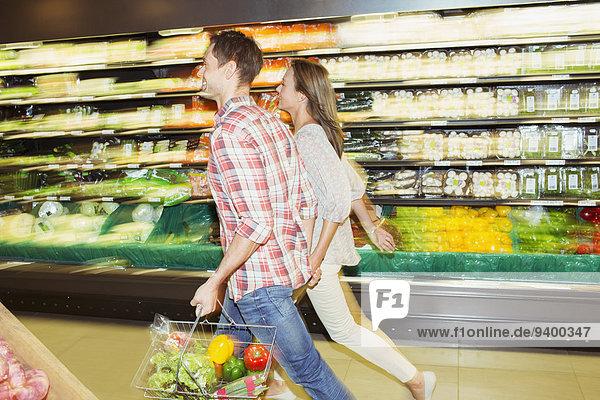 Verschwommener Blick auf das gemeinsame Einkaufen eines Paares im Lebensmittelladen