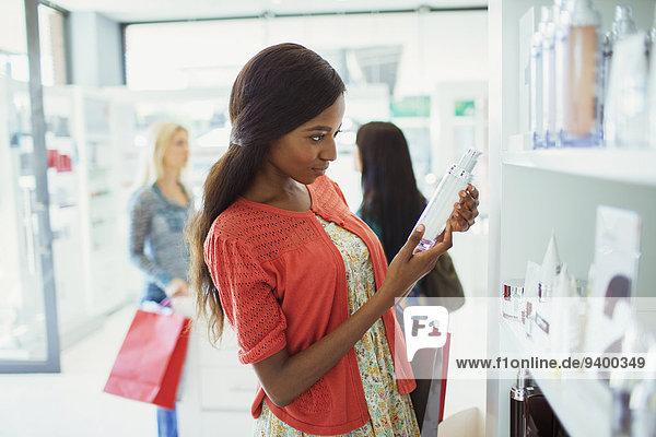 Frau untersucht Hautpflegemittel in der Apotheke Frau untersucht Hautpflegemittel in der Apotheke