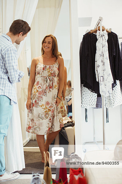 Mann hilft Freundin bei der Kleiderauswahl im Bekleidungsgeschäft