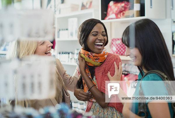 Frauen lachen gemeinsam im Bekleidungsgeschäft