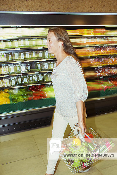 Verschwommene Ansicht der Frau mit vollem Einkaufskorb im Lebensmittelgeschäft