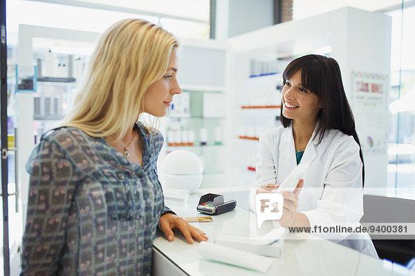 Frau im Gespräch mit Apothekerin in der Apotheke