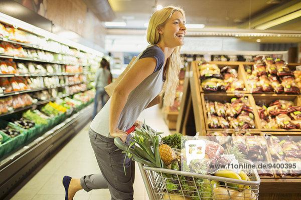 Frau spielt mit Einkaufswagen im Lebensmittelladen