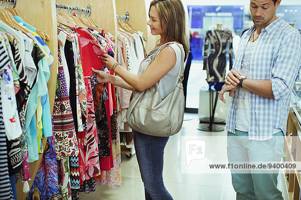 Bored man shopping with girlfriend in clothing store