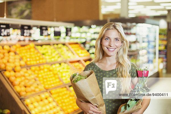 Frau mit Einkaufstaschen im Lebensmittelgeschäft