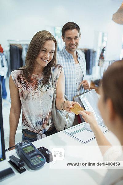 Frau bezahlt mit Kreditkarte im Bekleidungsgeschäft