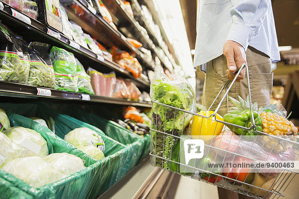 Man carrying full shopping basket in grocery store