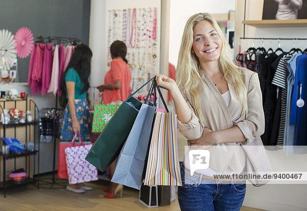Frau mit Einkaufstaschen im Bekleidungsgeschäft