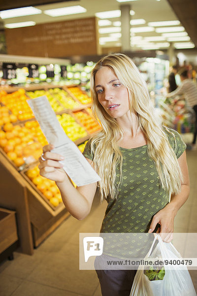 Frustrated woman reading receipt in grocery store