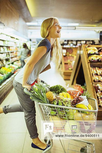 Frau spielt auf dem Einkaufswagen im Lebensmittelladen