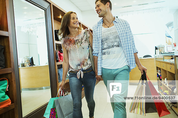 Couple carrying shopping bags in store