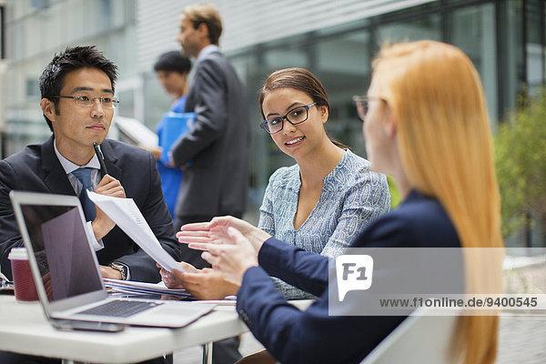 Geschäftsleute sprechen am Tisch im Freien