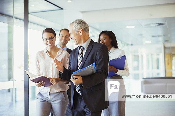 Geschäftsleute gehen und reden im Büro