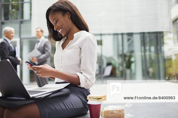 Geschäftsfrau auf der Bank sitzend mit dem Handy