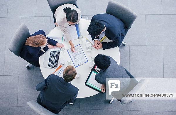 Geschäftsleute im Gespräch bei Tisch