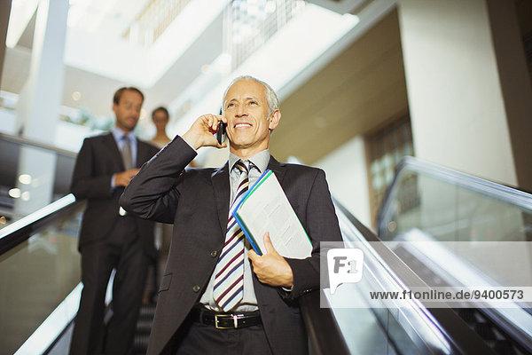 Geschäftsmann spricht auf dem Handy und fährt die Rolltreppe hinunter