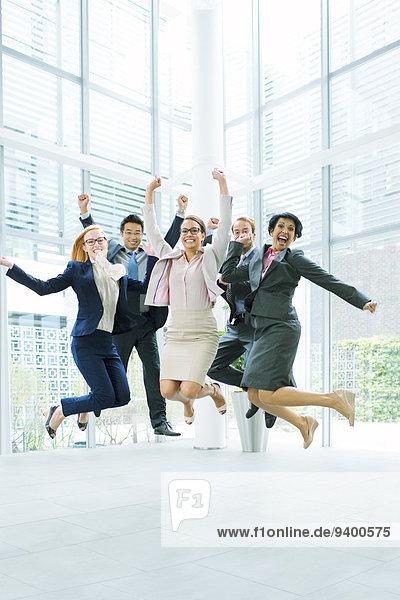 Geschäftsleute springen in Bürogebäude