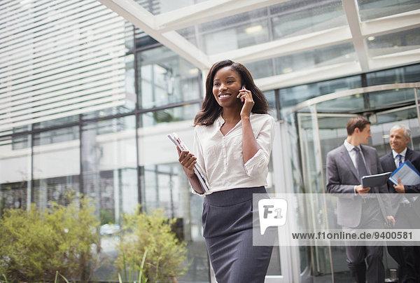 Geschäftsfrau spricht am Handy und verlässt das Bürogebäude