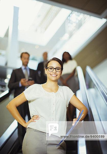 Geschäftsfrau auf Rolltreppe im Bürogebäude