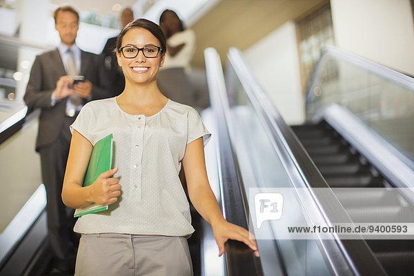 Geschäftsfrau geht im Bürogebäude die Rolltreppe runter