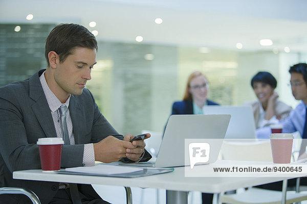 Geschäftsmann mit Handy im Bürogebäude Cafe