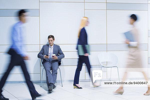 Geschäftsmann sitzend mit Handy im Bürogebäude