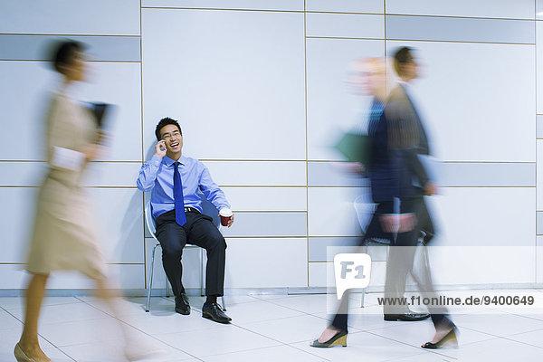 Geschäftsmann sitzend am Handy im Bürogebäude