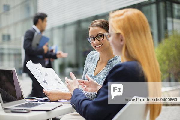 Geschäftsfrauen beim Betrachten von Dokumenten am Tisch im Bürogebäude