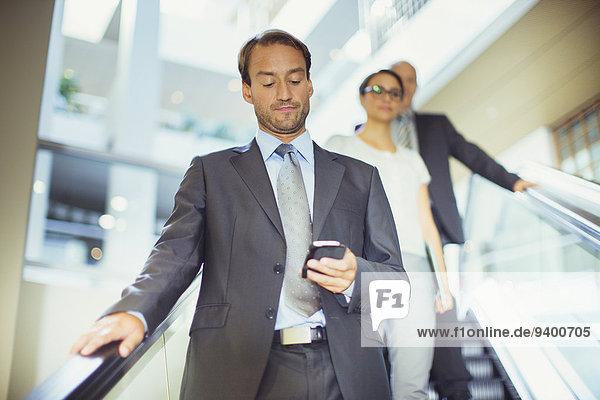 Geschäftsmann mit Handy auf Rolltreppe im Bürogebäude