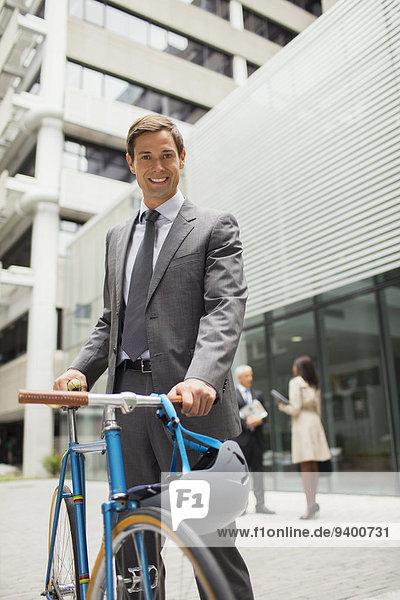 Geschäftsmann mit dem Fahrrad vor dem Bürogebäude