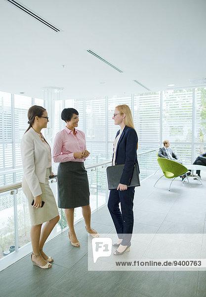 Businesswomen talking in office building